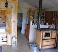 Cupboard bed and wood stove in tent